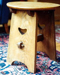 Small oak table by Liberty &  Co with squashed heart piercing, supports to top and pegged stretcher