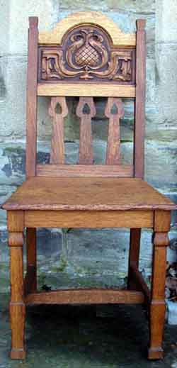 Oak hall chair with carved design of thistle and leaves, the heart pierced slats and chamfered legs are typical of Shapland and Petter design